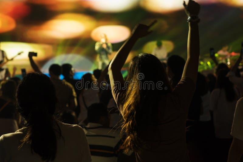 Πλήθος που απολαμβάνει τη συναυλία, μεγάλη ομάδα που γιορτάζει τις νέες διακοπές έτους, έννοια διασκέδασης υποβάθρου κομμάτων στοκ εικόνες