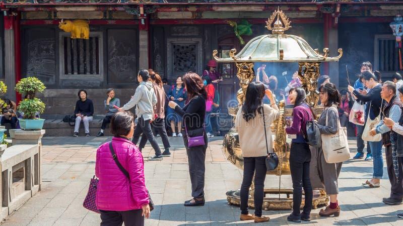 Πλήθος των ανθρώπων που προσεύχονται και που προσφέρουν το θυμίαμα με το χρυσό γιγαντιαίο καυστήρα θυμιάματος στο ναό Longshan στοκ φωτογραφία με δικαίωμα ελεύθερης χρήσης