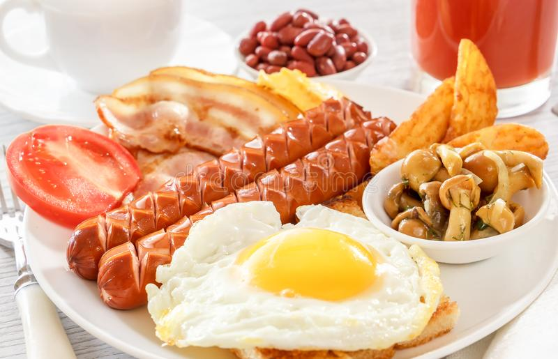 Πλήρες αγγλικό πρόγευμα - τηγανισμένο αυγό, λουκάνικα, μπέϊκον, φασόλια Ένα ποτήρι του φρέσκου χυμού Ένα φλυτζάνι του τσαγιού με  στοκ εικόνες με δικαίωμα ελεύθερης χρήσης