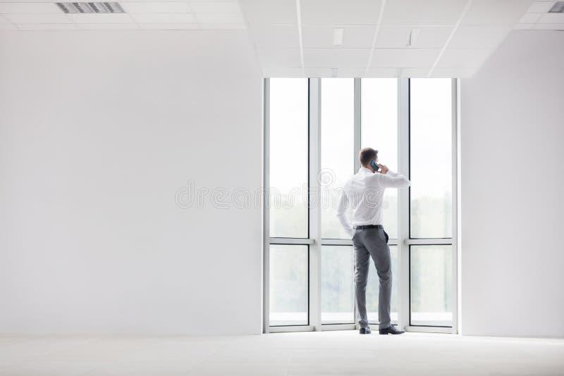 Πλήρες μήκος οπισθοσκόπο της νέας ομιλίας επιχειρηματιών στο smartphone στο νέο γραφείο στοκ φωτογραφίες