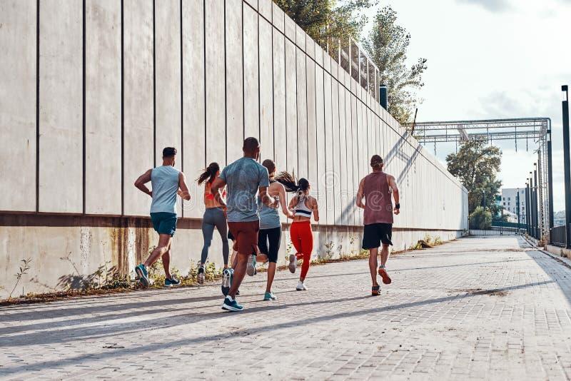 Πλήρες μήκος οπισθοσκόπο των νέων στην αθλητική ενδυμασία στοκ φωτογραφία