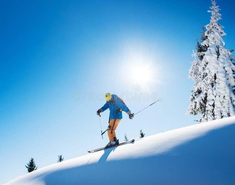 Πλήρες μήκος που πυροβολείται ενός επαγγελματικού σκιέρ freeride που κάνει σκι πάνω από το βουνό στοκ φωτογραφίες