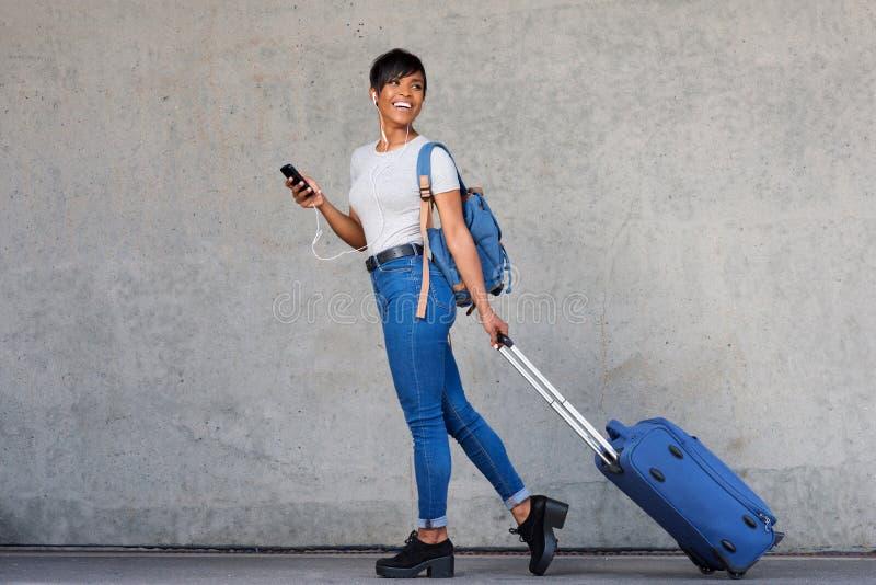 Πλήρες μήκος που ταξιδεύει τη νέα γυναίκα με το κινητές τηλέφωνο και τη βαλίτσα στοκ εικόνες