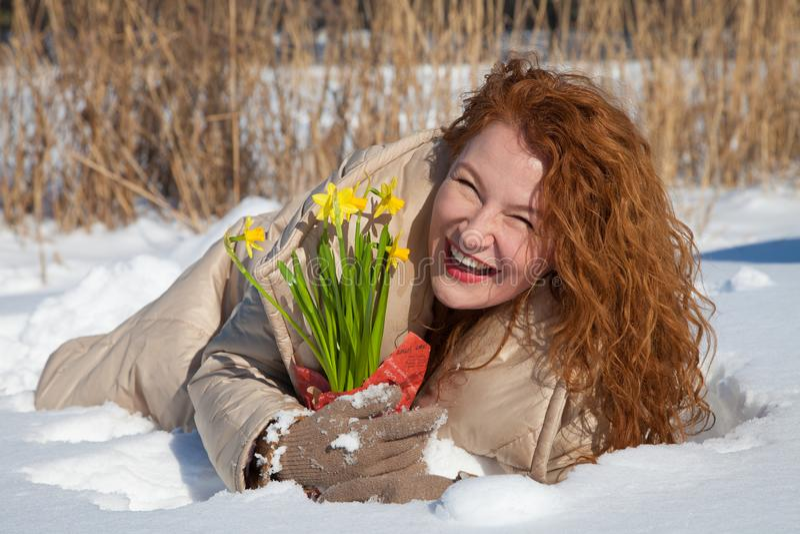 Πλήρες μήκος της ευτυχούς γυναίκας που βρίσκεται στην επιφάνεια χιονιού με τα κίτρινα narcissuses στοκ φωτογραφία με δικαίωμα ελεύθερης χρήσης