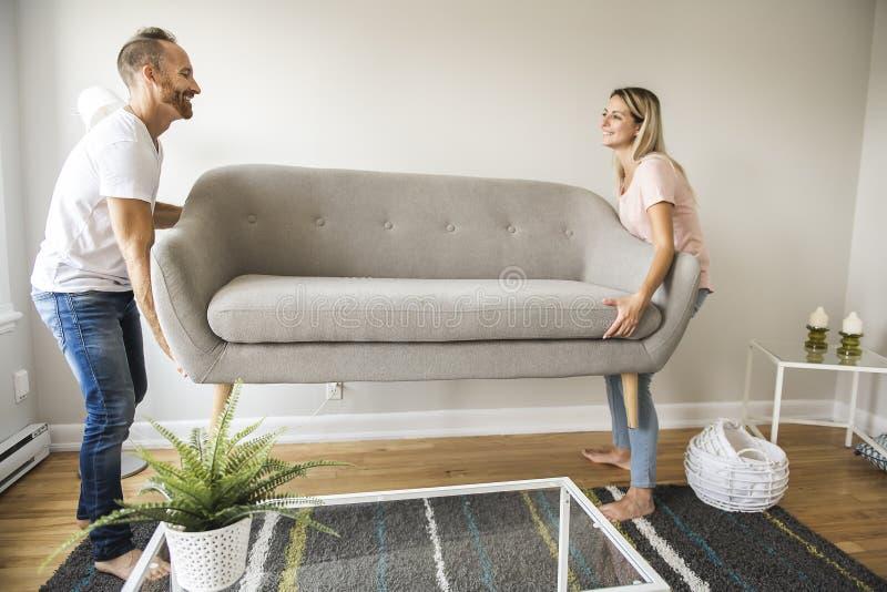 Πλήρες μήκος του ευτυχούς ζεύγους που τοποθετεί τον καναπέ στο καθιστικό του νέου σπιτιού στοκ εικόνα
