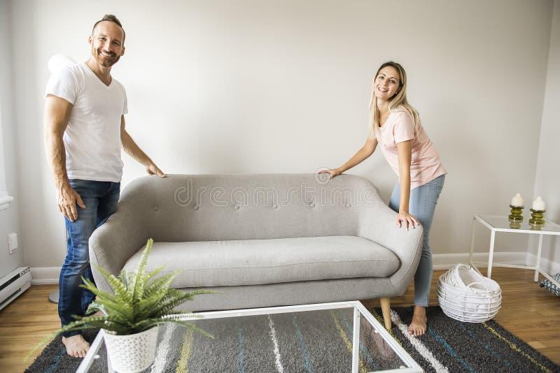 Πλήρες μήκος του ευτυχούς ζεύγους που τοποθετεί τον καναπέ στο καθιστικό του νέου σπιτιού στοκ φωτογραφία με δικαίωμα ελεύθερης χρήσης