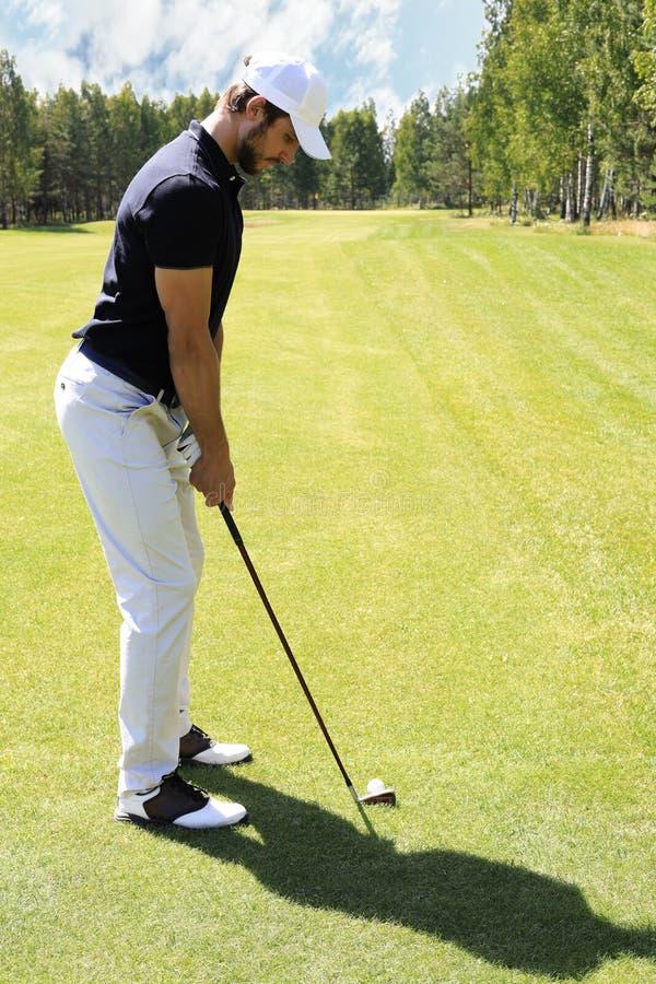 Πλήρες μήκος του παίζοντας γκολφ φορέων γκολφ την ηλιόλουστη ημέρα Επαγγελματικός αρσενικός παίκτης γκολφ που παίρνει τον πυροβολ στοκ εικόνες