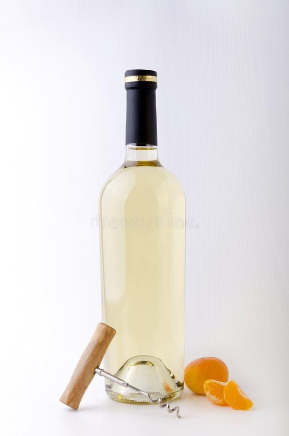 Πλήρες μπουκάλι του κρασιού, του ανοιχτήρι και tangerines στην άσπρη επιφάνεια r στοκ εικόνες