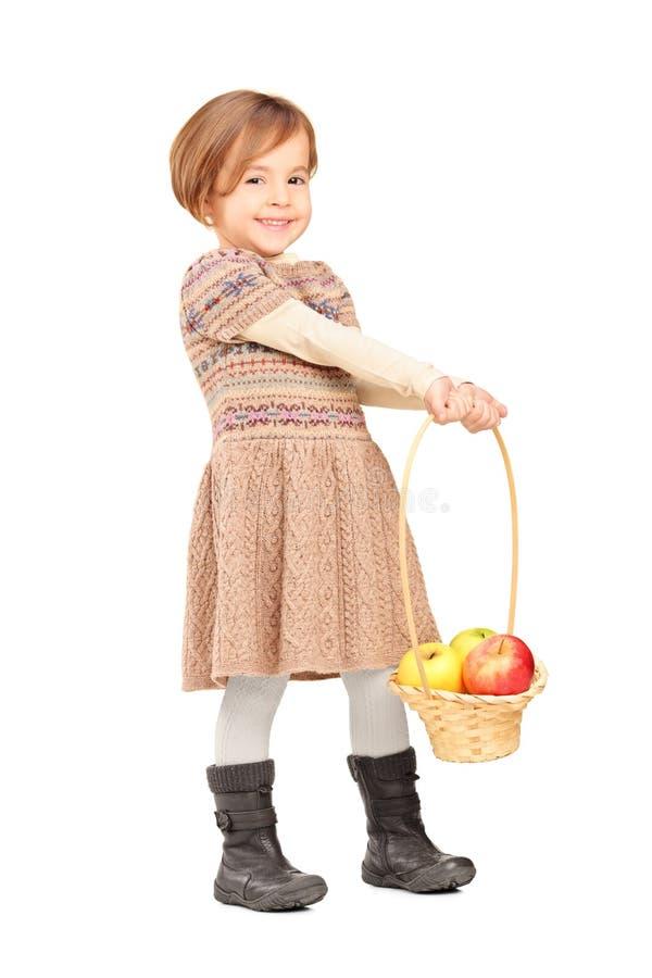 Πλήρες πορτρέτο μήκους ενός χαριτωμένου μικρού κοριτσιού που κρατά ένα καλάθι με στοκ εικόνες