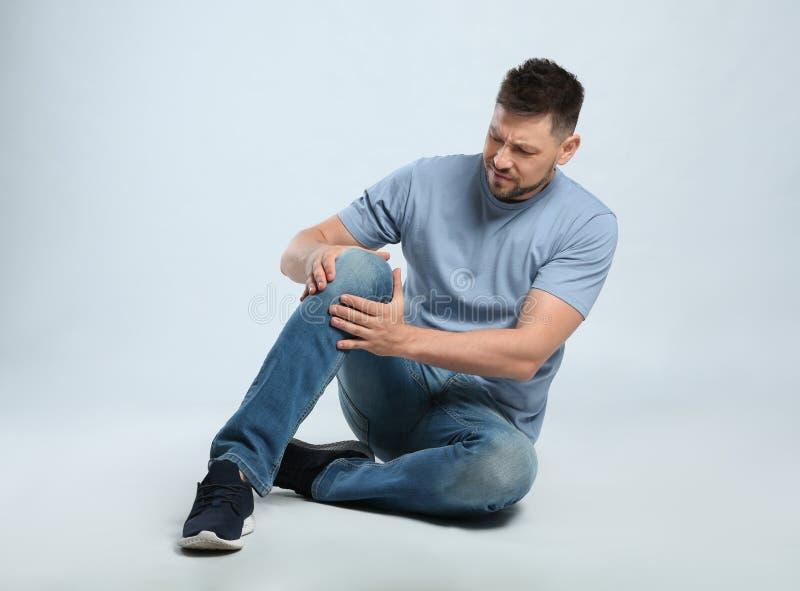 Πλήρες πορτρέτο μήκους του ατόμου με τα προβλήματα γονάτων που κάθονται στο γκρι στοκ εικόνα με δικαίωμα ελεύθερης χρήσης
