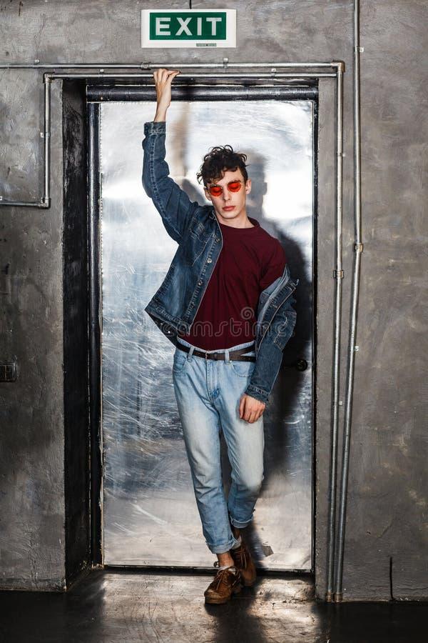 Πλήρες πορτρέτο μήκους του μοντέρνου νέου πρότυπου ατόμου μόδας στα φωτεινά κόκκινα γυαλιά ηλίου και της περιστασιακής τοποθέτηση στοκ εικόνες