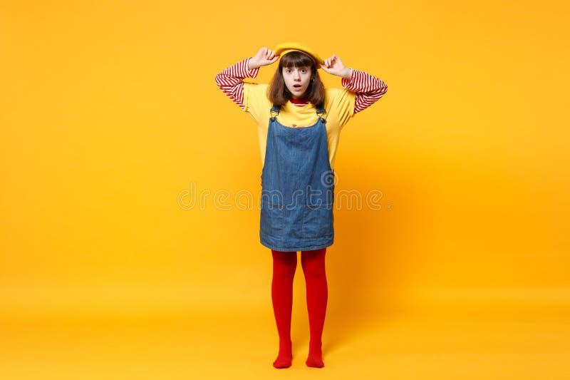 Πλήρες πορτρέτο μήκους του μπερδεμένου εφήβου κοριτσιών γαλλικό beret εκμετάλλευσης τζιν sundress που απομονώνεται στον κίτρινο τ στοκ φωτογραφίες