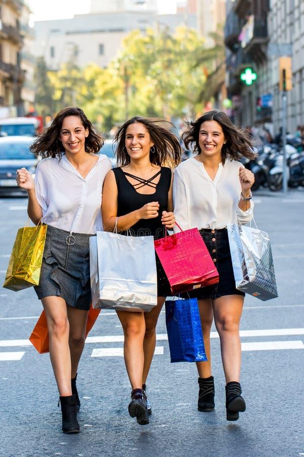 Πλήρες πορτρέτο μήκους τριών θηλυκών αγοραστών με τις τσάντες στην πόλη στοκ εικόνες