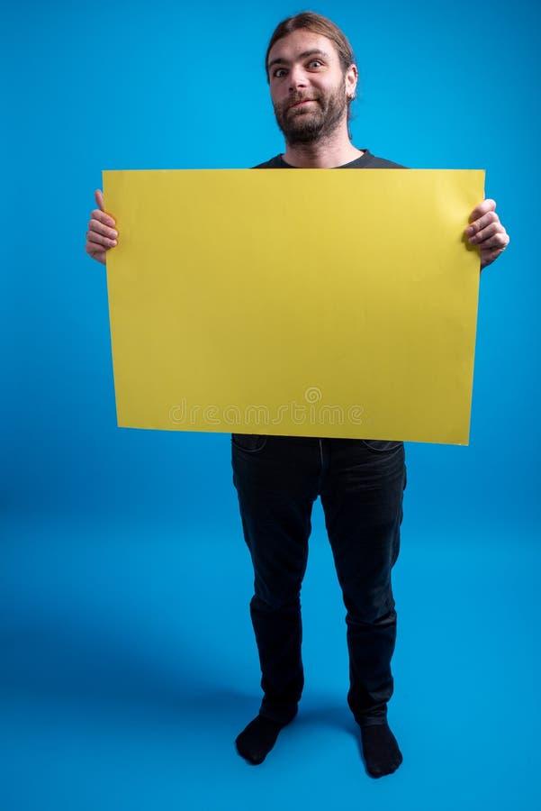 Πλήρες πορτρέτο του αστείου ατόμου που κρατά έναν πίνακα διαφημίσεων χαρτονιού στοκ εικόνα με δικαίωμα ελεύθερης χρήσης
