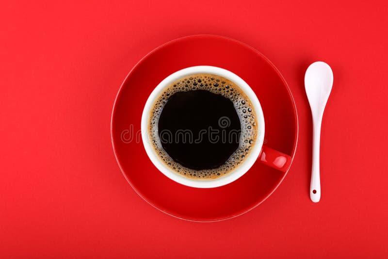 Πλήρες φλυτζάνι του μαύρων καφέ και του πιατακιού πέρα από το κόκκινο στοκ εικόνα με δικαίωμα ελεύθερης χρήσης