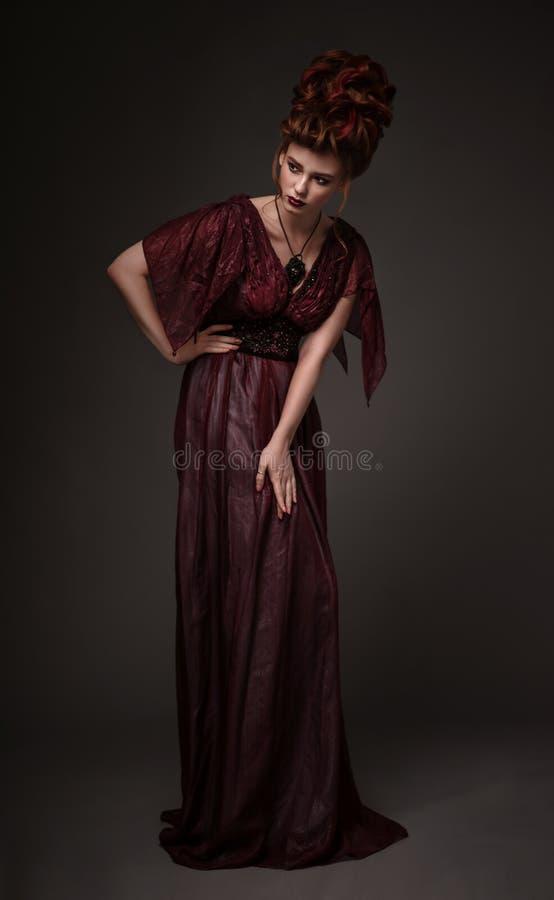 Πλήρης άποψη μήκους της γυναίκας με το μπαρόκ καφέ φόρεμα hairstyle και βραδιού στοκ φωτογραφίες