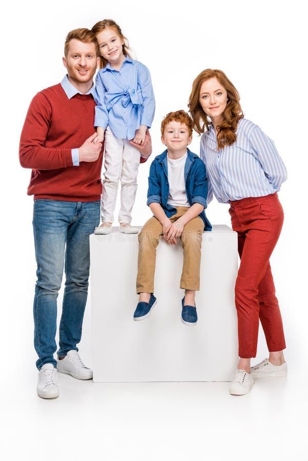 πλήρης άποψη μήκους της ευτυχούς κοκκινομάλλους οικογένειας που χαμογελά στη κάμερα στοκ φωτογραφίες με δικαίωμα ελεύθερης χρήσης