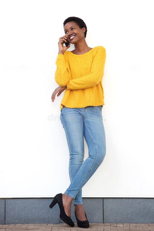 Πλήρης γυναίκα αφροαμερικάνων σωμάτων όμορφη νέα που χαμογελά ενάντια στον άσπρο τοίχο και που μιλά με το κινητό τηλέφωνο στοκ εικόνες με δικαίωμα ελεύθερης χρήσης