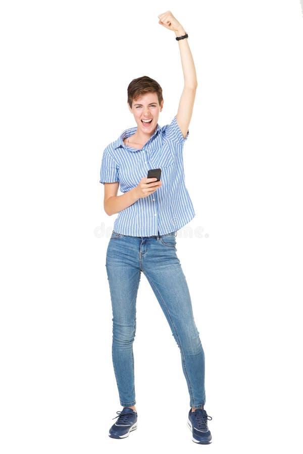 Πλήρης ευτυχής νέα γυναίκα μήκους με το κινητό τηλέφωνο ενθαρρυντικό στοκ εικόνα