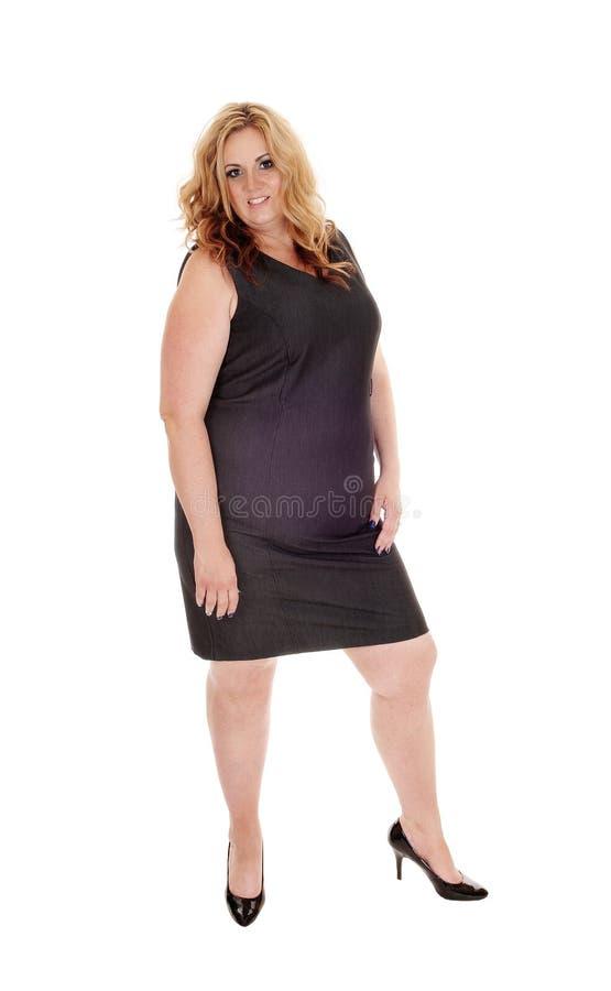 Πλήρης - μεγέθους γυναίκα που στέκεται στο μαύρο φόρεμα στοκ φωτογραφία