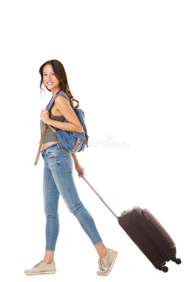 Πλήρης πλευρά σωμάτων του ευτυχούς ασιατικού θηλυκού ταξιδιωτικού περπατήματος με τη βαλίτσα και την τσάντα στο απομονωμένο άσπρο στοκ εικόνες