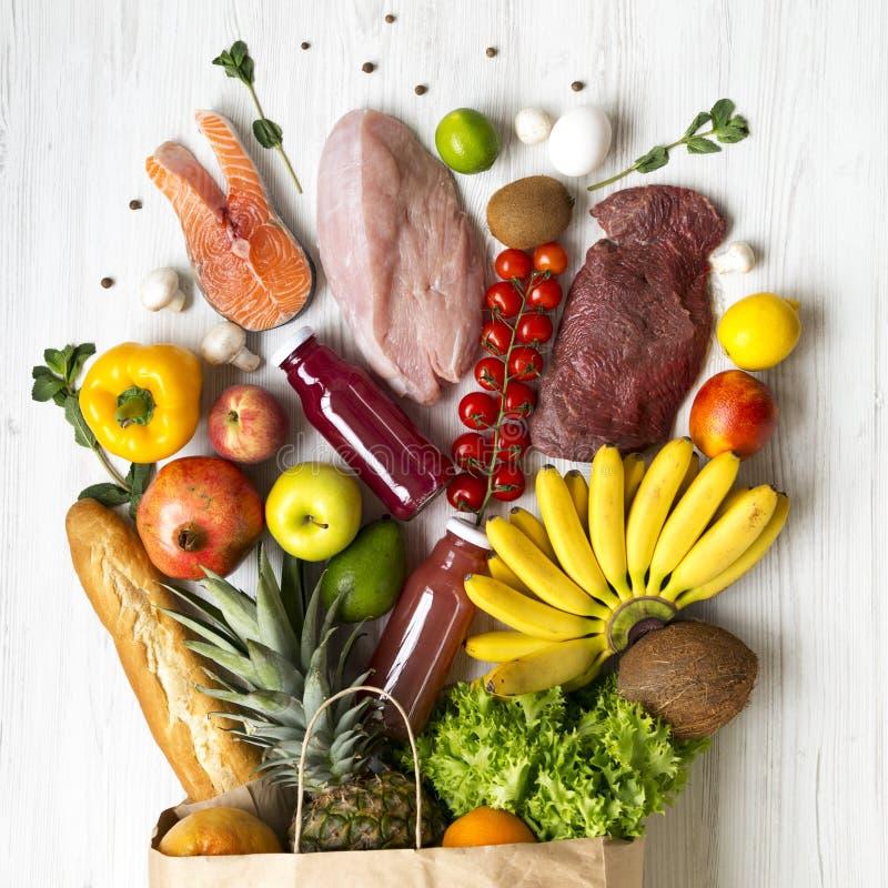 Πλήρης τσάντα εγγράφου των υγιών ακατέργαστων τροφίμων στο άσπρο ξύλινο υπόβαθρο Υπόβαθρο παντοπωλείων Τοπ άποψη, άνωθεν, υπερυψω στοκ εικόνα με δικαίωμα ελεύθερης χρήσης