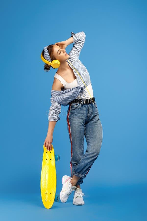 Πλήρης φωτογραφία μήκους της αρκετά ξένοιαστης νέας γυναίκας με την πένα ή skateboard τη μουσική ακούσματος με τα κίτρινα ακουστι στοκ εικόνες
