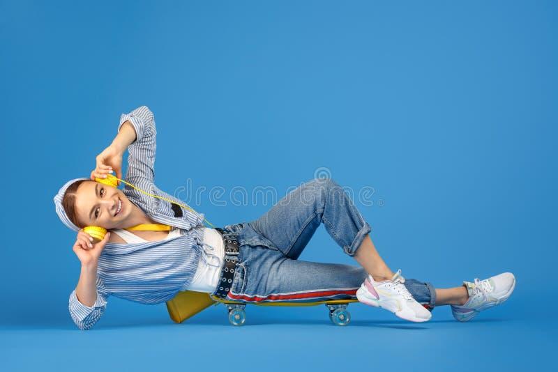 Πλήρης φωτογραφία μήκους της ευτυχούς ξένοιαστης νέας γυναίκας με τα κίτρινα ακουστικά που κάθεται στην πένα ή skateboard πέρα απ στοκ φωτογραφία με δικαίωμα ελεύθερης χρήσης