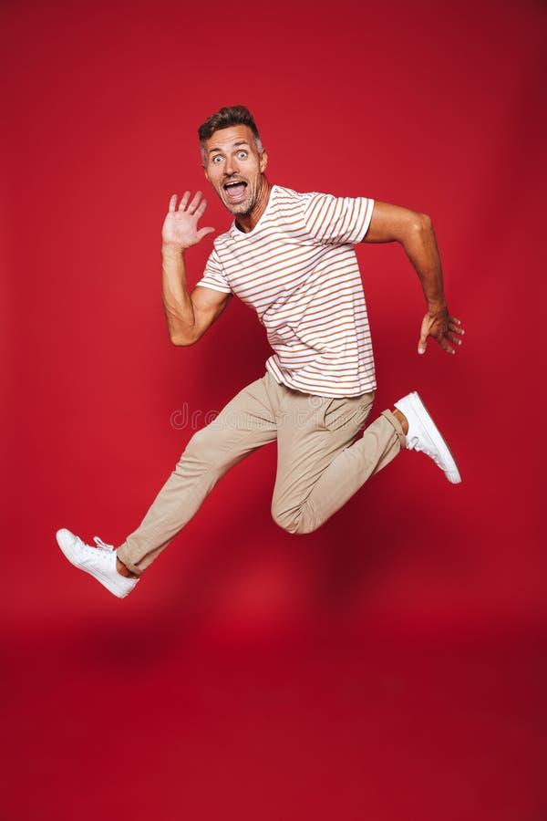 Πλήρης φωτογραφία μήκους του χαρούμενου ατόμου στο ριγωτά άλμα μπλουζών και το s στοκ φωτογραφία