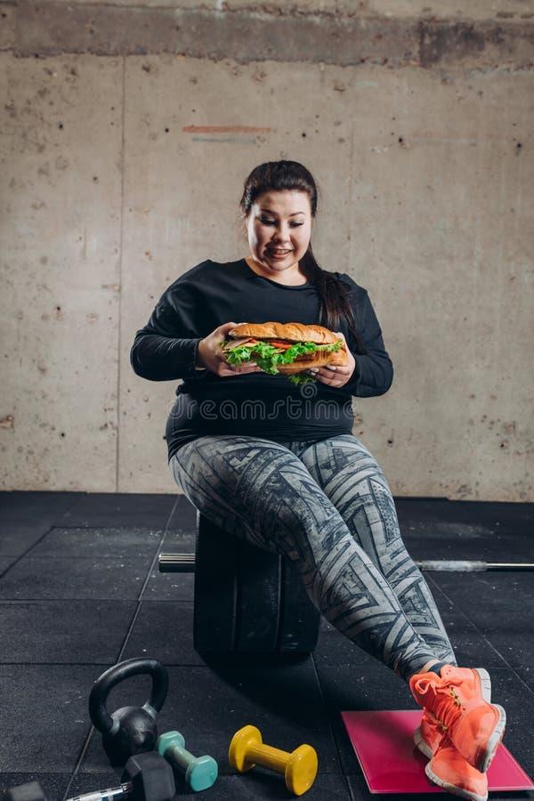 Πλήρης φωτογραφία μήκους το ευτυχές παχύσαρκο κορίτσι πρόκειται να φάει ένα χάμπουργκερ στοκ εικόνες