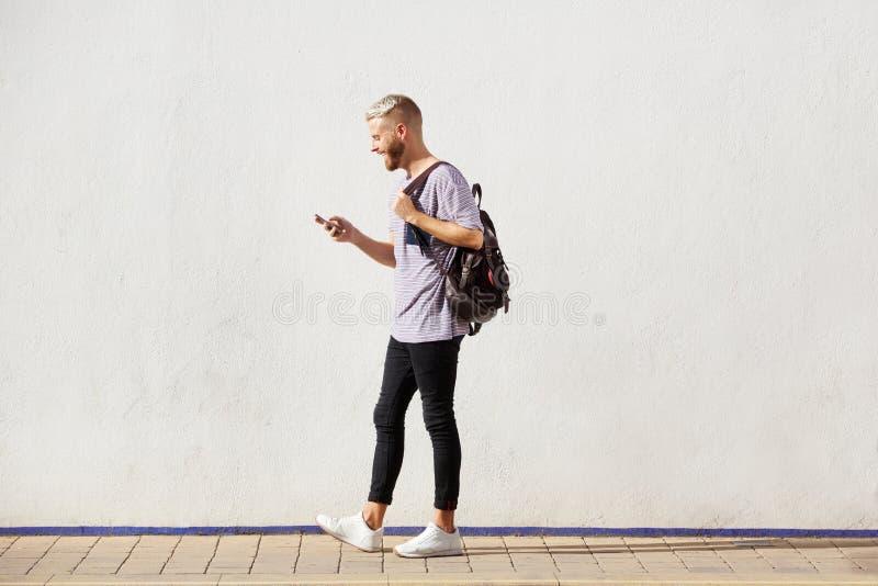 Πλήρης όμορφος νεαρός άνδρας μήκους που περπατά με το τηλέφωνο κυττάρων στοκ εικόνα με δικαίωμα ελεύθερης χρήσης