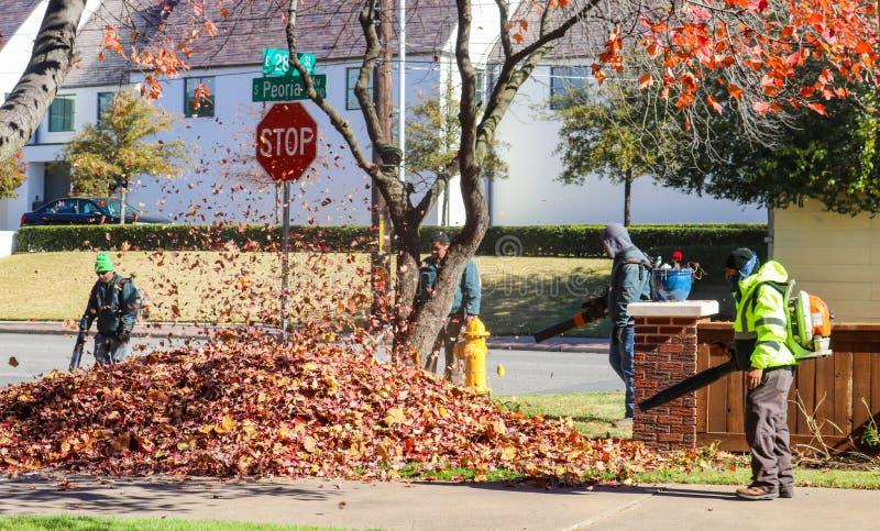 Πλήρωμα των εργαζομένων με τα σακίδια πλάτης και των σακακιών που φυσούν τα φύλλα σε έναν σωρό με τα φύλλα που στροβιλίζονται τον στοκ φωτογραφίες