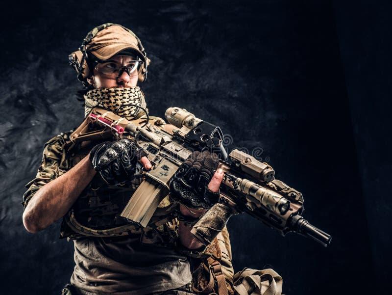 Πλήρως εξοπλισμένος στρατιώτης στην ομοιόμορφη εκμετάλλευση κάλυψης ένα επιθετικό τουφέκι Φωτογραφία στούντιο ενάντια σε έναν σκο στοκ εικόνες
