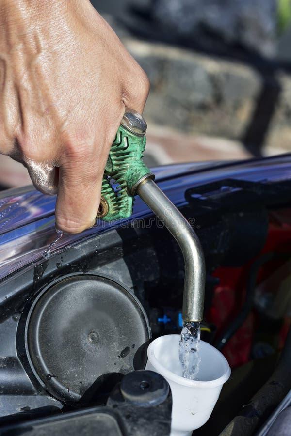Πλήρωση της δεξαμενής του ρευστού πλυντηρίων ανεμοφρακτών στοκ εικόνες
