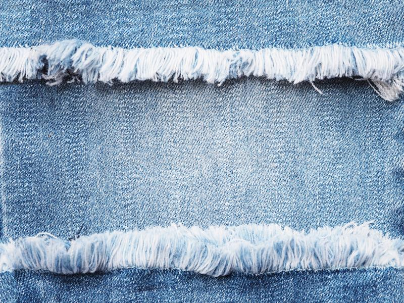Πλαίσιο ακρών του μπλε τζιν που σχίζεται πέρα από το υπόβαθρο σύστασης τζιν στοκ φωτογραφία με δικαίωμα ελεύθερης χρήσης