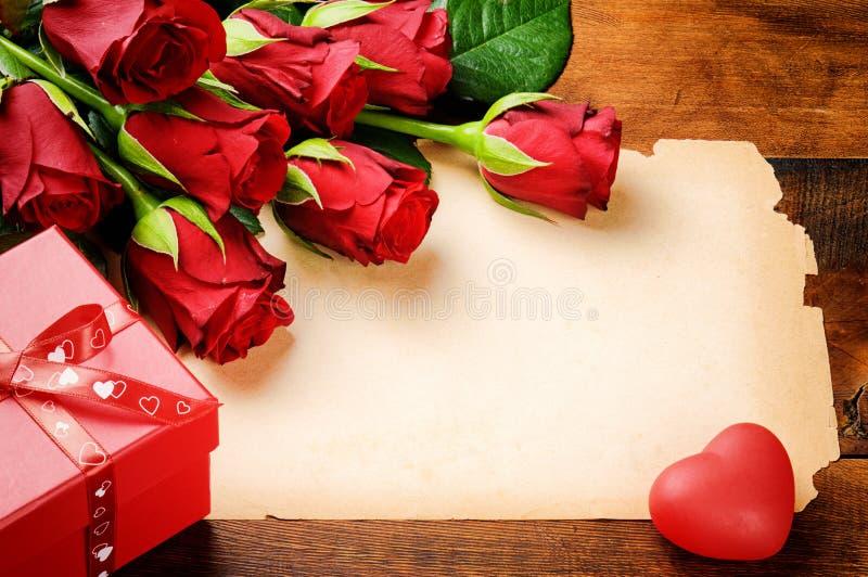 Πλαίσιο βαλεντίνου με τα κόκκινα τριαντάφυλλα και το εκλεκτής ποιότητας έγγραφο στοκ εικόνα