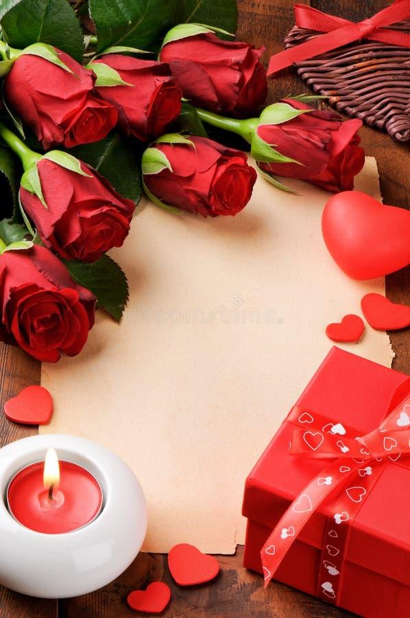 Πλαίσιο βαλεντίνου με τα κόκκινα τριαντάφυλλα και το εκλεκτής ποιότητας έγγραφο στοκ εικόνες