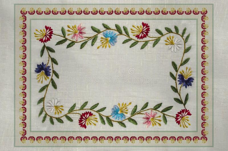 Πλαίσιο με τα κεντημένα σχέδια βελονιών σατέν των branchlets με τα φύλλα, και κόκκινο, μπλε, πορφύρα, cornflowers στο ύφασμα βαμβ διανυσματική απεικόνιση