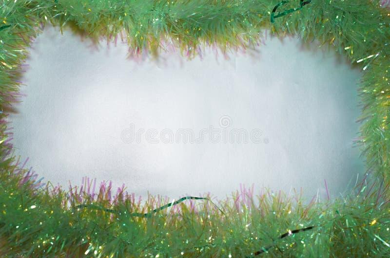 Πλαίσιο πράσινο tinsel Χριστουγέννων στο ασημένιο υπόβαθρο στοκ εικόνες
