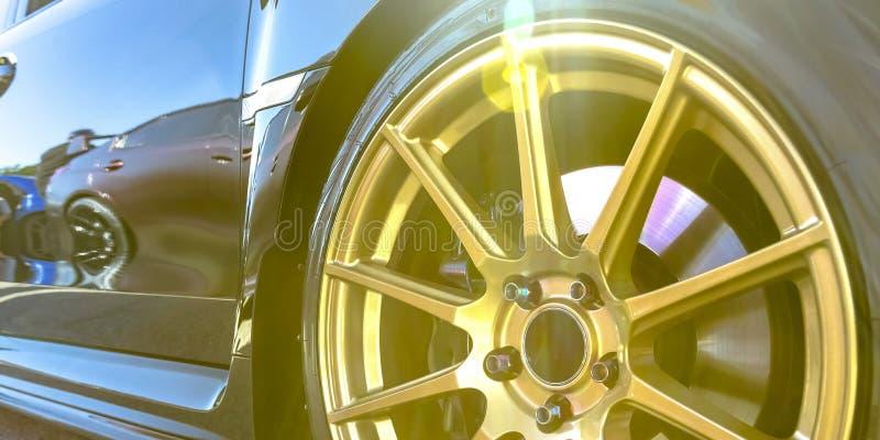 Πλαίσιο ροδών με τα χρυσά spokes ενός αντανακλαστικού αυτοκινήτου στοκ εικόνες