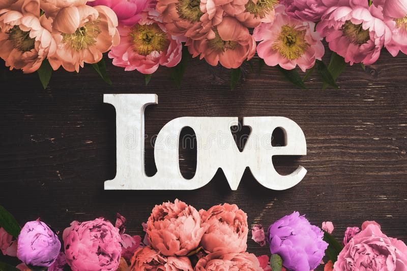 Πλαίσιο των λουλουδιών στο ξύλινο υπόβαθρο και την αγάπη ` λέξης ` στοκ φωτογραφίες με δικαίωμα ελεύθερης χρήσης