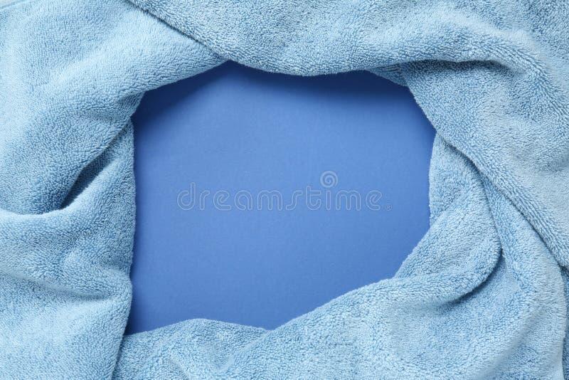 Πλαίσιο φιαγμένο από μαλακή μπλε πετσέτα στο υπόβαθρο χρώματος στοκ φωτογραφία
