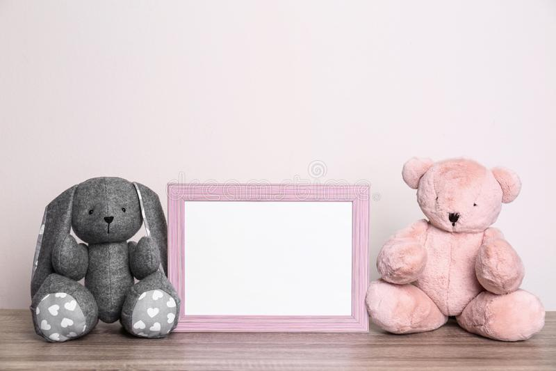 Πλαίσιο φωτογραφιών και λατρευτά παιχνίδια στον πίνακα στο ελαφρύ κλίμα Στοιχεία δωματίων παιδιών στοκ εικόνα