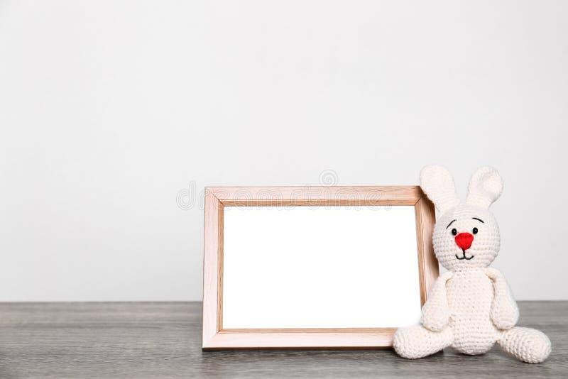 Πλαίσιο φωτογραφιών και λατρευτό λαγουδάκι παιχνιδιών στον πίνακα στο ελαφρύ κλίμα Στοιχεία δωματίων παιδιών στοκ φωτογραφία με δικαίωμα ελεύθερης χρήσης