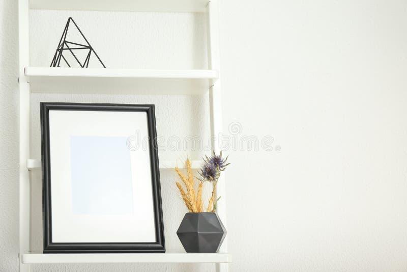 Πλαίσιο φωτογραφιών με το βάζο στο ράφι στο ελαφρύ κλίμα στοκ φωτογραφία