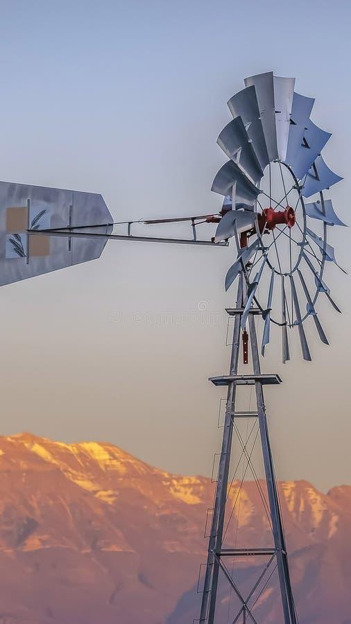Πλαίσιο Windpump πανοράματος με ένα τραχύ χρυσό βουνό και ένα νεφελώδες υπόβαθρο ουρανού στοκ εικόνα με δικαίωμα ελεύθερης χρήσης