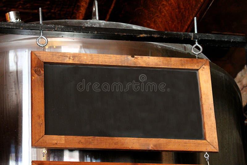 Πλαισιωμένος ξύλο πίνακας κιμωλίας μπροστά από μια δεξαμενή ζυθοποιείων στοκ εικόνα με δικαίωμα ελεύθερης χρήσης