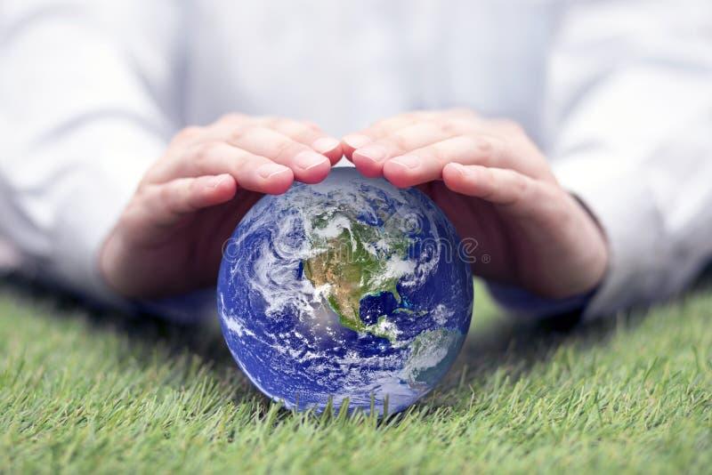 Πλανήτης Γη που προστατεύεται με το χέρι στοκ εικόνα