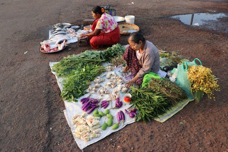 Πλανόδιοι πωλητές των ψαριών και των λαχανικών που στρώνουν το ύφασμα για να πωλήσει τα προϊόντα στο δρόμο σε Yangon στοκ εικόνα