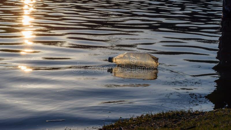 Πλαστικά απορρίματα μπουκαλιών νερό που επιπλέουν στη λίμνη στο ηλιοβασίλεμα στοκ εικόνα με δικαίωμα ελεύθερης χρήσης